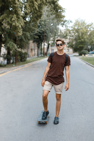 Attractive cool young hipster man in sunglasses in a stylish T-shirt in summer shorts in sneakers riding a skateboard in the park on a warm summer day. Handsome guy travels around the city.