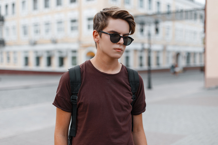 Attractive stylish young hipster man in stylish sunglasses in a fashionable brown t-shirt with a sports backpack walks through the city. Modern guy on vacation. Men's fashion.