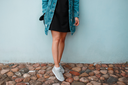 Slender legs of a young stylish woman in fashionable summer shoes. Modern youth street style.
