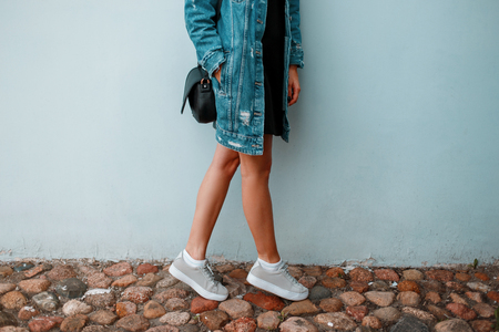 Beautiful female legs with stylish sneakers near blue wall. Fashion Denim Clothing