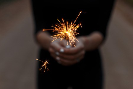 Woman in a black T-shirt celebrates the holiday with amazing sparklers. Female hands with sparkler close-up. Focus on bright fire.