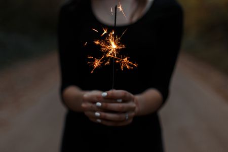 Young woman holds a bright orange festive sparkler in her hands. Girl celebrates birthday. Female hands closeup. Stock Photo
