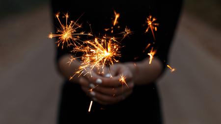 Increíbles bengalas festivas en manos de una mujer joven. Niña celebra feliz cumpleaños. Chispas de color naranja brillante con un primer plano.