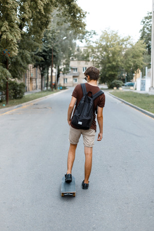 Modern young handsome man in summer shorts with a backpack in a hipster t-shirt is riding along the road on a skateboard in the park. American guy travels around the city. View from the back. Reklamní fotografie