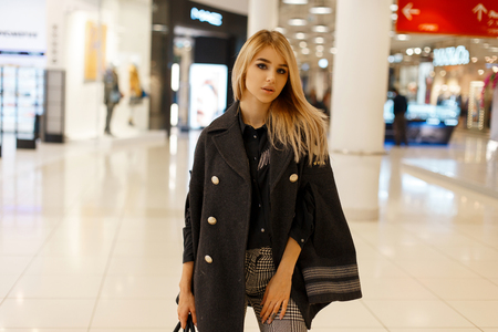 Sexy elegant young woman in a trendy gray coat in a black shirt in vintage gray checkered pants with a leather handbag is poses in a modern shopping center. Cute fashion girl model.