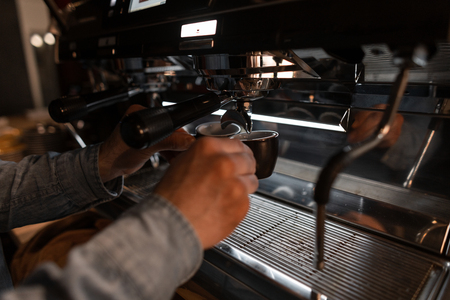 Young barista makes tasty hot coffee in a professional coffee machine. Modern coffee machine pours espresso into a black mug. male hands with coffee close up. Stock Photo