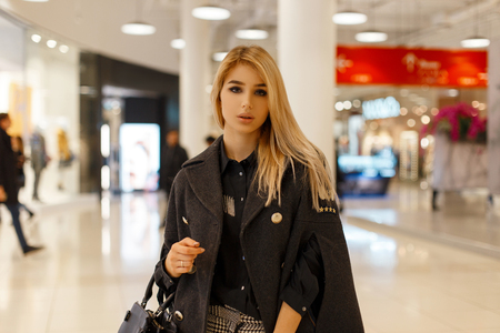Pretty stylish young woman with blond hair in a trendy gray coat with a leather stylish bag in a fashionable blouse in checkered pants walks in a bright modern shopping center. Elegant girl shopping.