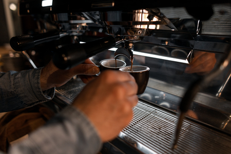 Professional young barista man in cafe prepares fragrant hot tasty espresso. Service Concept. Cups and male hands closeup. Wonderful morning drink.