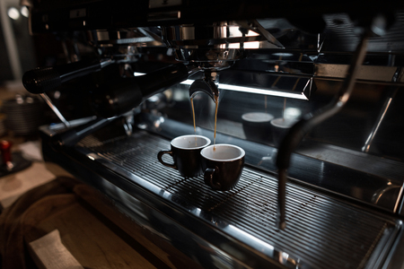 Two black coffee cups are in a modern professional coffee machine. Coffee machine pours hot americano. Wonderful morning drink.