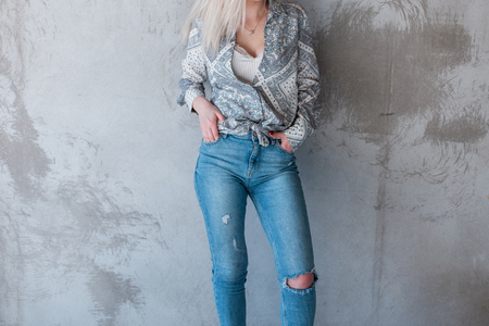 Young sexy stylish woman in a summer fashionable shirt in ripped stylish jeans is standing near a gray concrete wall. Modern street style women's clothing.