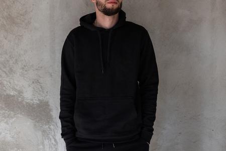 Modieuze jonge man met een baard in zwarte stijlvolle kleding staat binnenshuis in de buurt van een betonnen vintage muur. Trendy coole kerel. Moderne herenmode. Detailopname.