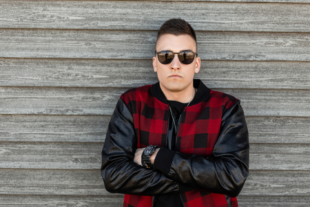 American serious young hipster man in black sunglasses in a vintage red checkered jacket in a black t-shirt with a stylish hairstyle near a wooden wall outdoors. Handsome stylish guy.