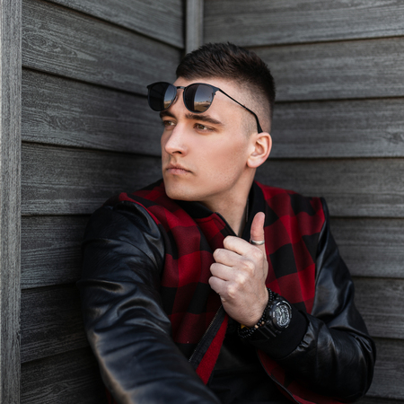 Urban young hipster man in black sunglasses in a trendy red checkered jacket with leather sleeves with a fashionable hairstyle posing near a wooden wall on a summer day. Handsome stylish guy model. 免版税图像