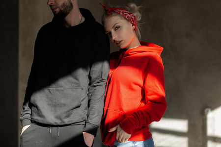 Beautiful young stylish couple in trendy hoodie indoors with sunshine. Hipster girl in red hoodie and handsome man with beard in blue hoodie in studio Imagens