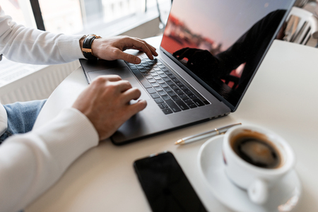 Il giovane uomo d'affari professionista utilizza un computer portatile per lavoro. Blogger funziona al computer. Vista laterale delle mani dell'uomo e del desktop, su cui si trova un moderno laptop, una tazza di caffè e un telefono.