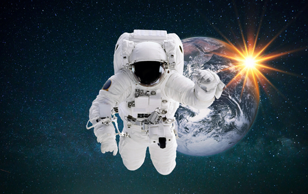 Spaceman in outer space flies near the planet Earth at sunset. Astronaut performs space mission against the stars