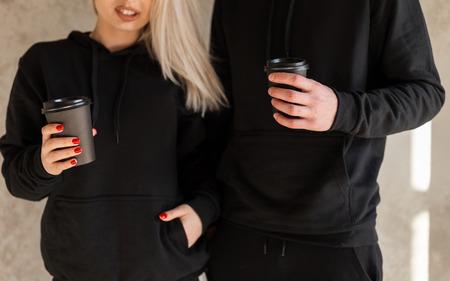 Giovani donne felici bionde con un giovane uomo alla moda con la barba in abiti neri alla moda sono in piedi vicino al muro in casa e tengono il caffè in mano. Pausa caffè. Avvicinamento.