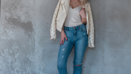 Young fashionable woman fashion model with a slim body in a stylish white t-shirt in vintage ripped jeans in a leather fashionable jacket with metal rivets near a gray wall. Female body close-up.