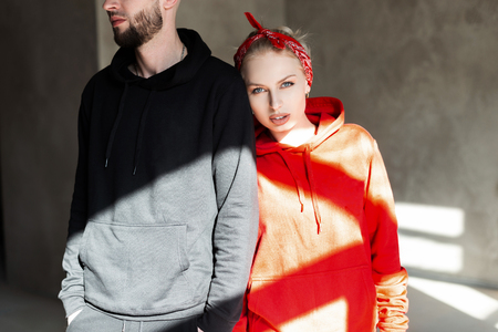 Stylish beautiful fashionable couple in fashion black and red hoodie indoors with sunlight. Pretty hipster woman in a red hoodie standing near a style man in a black sweatshirt