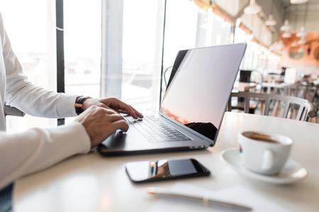 Sukcesy biznesmen pracuje za laptopem w kawiarni. Bloger prowadzi swój osobisty blog na laptopie. Zbliżenie
