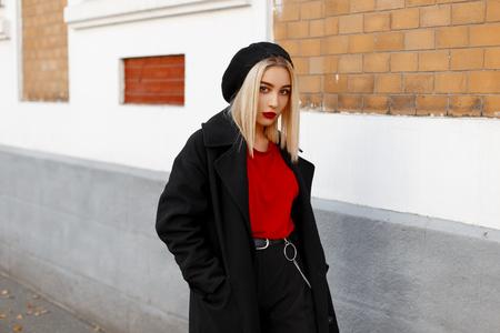 Glamorosa hermosa joven moderna con una boina negra en una camiseta roja con un abrigo largo de moda en elegantes pantalones cerca de un edificio vintage en un día de otoño. Chica urbana de moda en un paseo.