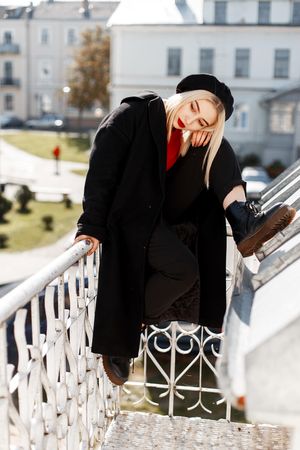 Pretty stylish young blond woman in an elegant coat in boots in a black trendy beret with red lips posing sitting on a vintage balcony on a bright sunny day. Modern attractive girl relaxes outdoors.