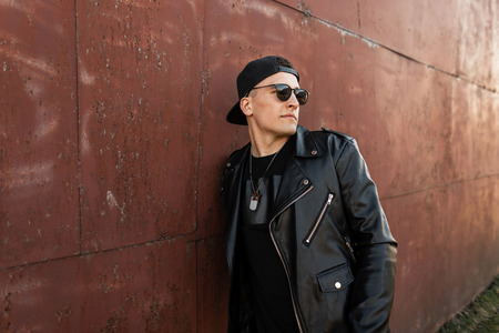 American young hipster man in stylish baseball cap in dark sunglasses in a trendy leather jacket in jeans in a stylish black t-shirt relaxes near a rusty metal wall. Cool guy enjoys the rest.