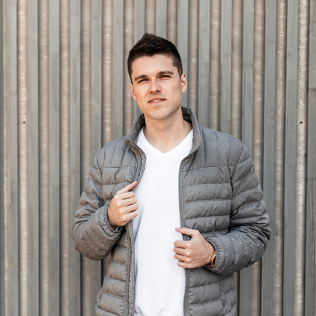 Joyful young attractive man in a fashionable gray spring jacket in a white trendy t-shirt with a stylish hairstyle stands near a wooden vintage wall outdoors. Modern American guy. Men's fashion. Foto de archivo - 121441006