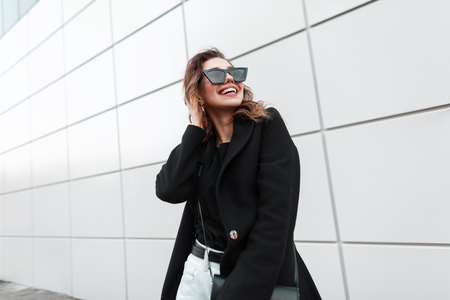 Joyful young woman hipster in sunglasses in a trendy coat in a T-shirt with a stylish leather handbag with a  cute smile in vintage jeans is standing near a modern gray building in the city.Happy girl