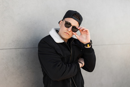 Young attractive hipster man in a trendy baseball cap in stylish sunglasses in a vintage black jacket with a white collar poses for a spring day in the city near a modern building. American guy. Foto de archivo - 121441074