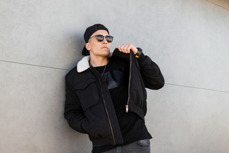 American young hipster man in stylish baseball cap in dark sunglasses in a fashionable black jacket with white fur in jeans in a black T-shirt relaxes near the gray wall. Ð¡ool guy is enjoying the rest Foto de archivo - 121441155