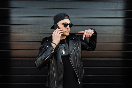 Young handsome attractive hipster man in a stylish leather jacket in a trendy black cap in dark fashionable sunglasses talking on my mobile phone near a wooden black building. Nice american guy. Foto de archivo - 121441220