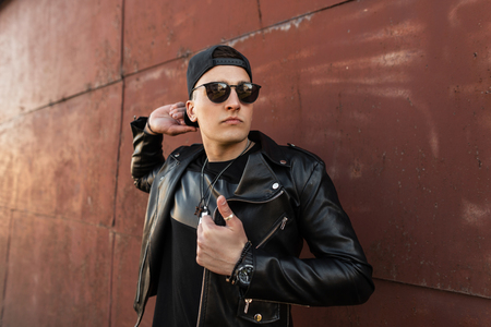 Handsome young man hipster in a stylish leather black jacket in a trendy black cap in dark fashionable sunglasses in a black T-shirt stands near a vintage metal wall outdoors. Attractive guy model.