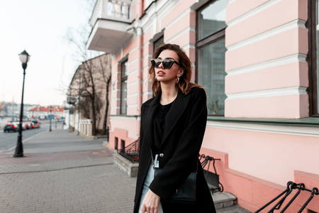 Fashionable modern young woman hipster in a black elegant coat in a T-shirt in jeans in stylish sunglasses walking down the street near vintage buildings. European girl travels around the city. Spring Stock Photo