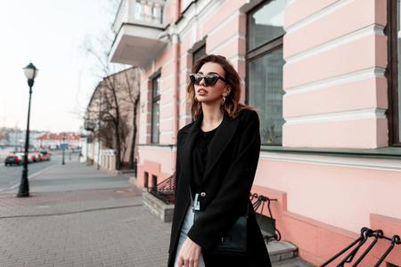 Modischer, moderner Hipster der jungen Frau in einem schwarzen eleganten Mantel in einem T-Shirt in Jeans in stylischer Sonnenbrille, der die Straße in der Nähe von Vintage-Gebäuden entlang geht. Europäisches Mädchen reist durch die Stadt. Feder Standard-Bild
