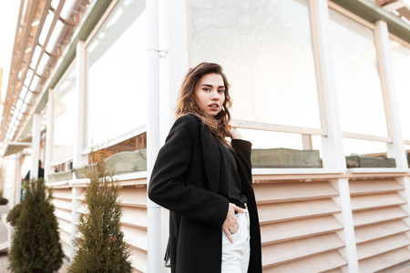 Pretty young elegant woman in a T-shirt in a trendy black coat in jeans is standing near a modern summer cafe and enjoys a spring day. Beautiful girl for a walk. New collection of women's clothing.