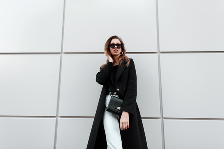 Pretty stylish hipster young woman in trendy black long coat in white jeans with a vintage leather bag in stylish dark sunglasses posing near a modern white wall. Elegant beautiful girl on a walk.