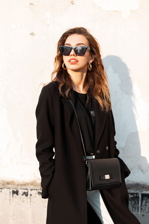 Young elegant hipster woman in trendy sunglasses in a long black coat in jeans with a handbag near a white building enjoys the sunset. Beautiful girl for a walk. New collection of women's clothing.