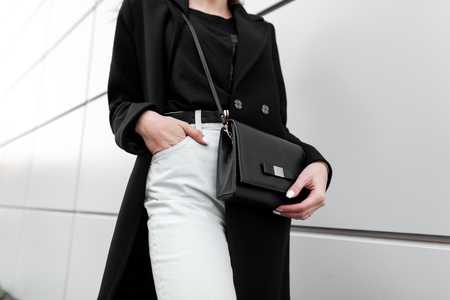 Young stylish woman in a fashionable long black coat in vintage white jeans in a black trendy t-shirt with a leather stylish black handbag is standing outdoors. Modern women's fashion. Spring-Autumn.
