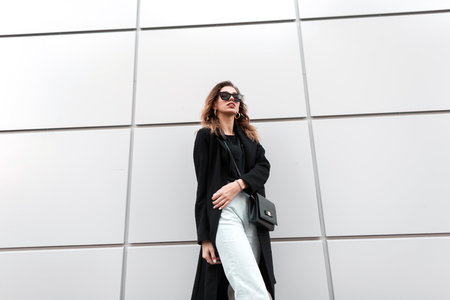 Fashionable young hipster woman in stylish clothes with a leather vintage handbag in trendy black sunglasses posing near a modern building in the city. Elegant girl. New collection of womens clothing