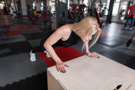 Slim young woman in black clothes does push-ups on a wooden box in the gym. Girl is engaged in fitness indoors.