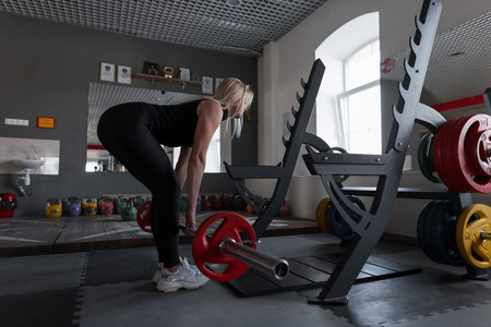 Young woman doing heavy exercise at the gym with a barbell. Girl in great shape doing squats in a fitness studio. Side view.