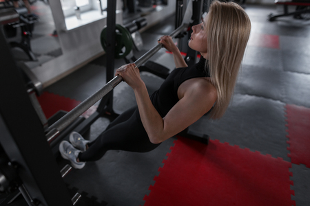 Attractive young woman blonde in stylish black sportswear engaged in fitness on a metal simulator. Girl goes in for sports in the gym. Healthy lifestyle.