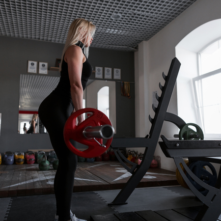 Young attractive woman in black sportswear in sneakers raises the barbell in training in the gym. Girl doing strength exercises. Stock fotó