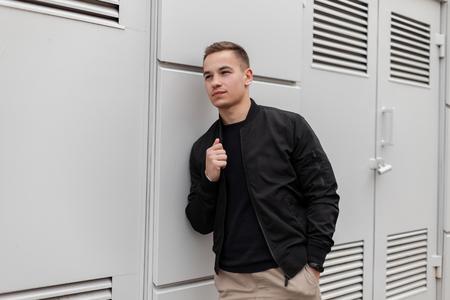 Hombre de moda atractivo joven en una chaqueta con estilo vintage en pantalones beige en una camiseta se relaja de pie cerca de una pared de metal gris cerca del edificio. Modern American está descansando en un día de primavera. Moda.