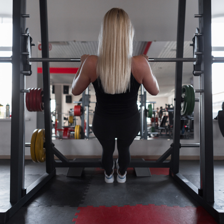 Athletic trainer of a young woman in black sportswear in gym sneakers. Girl doing exercises in a fitness studio. Back view
