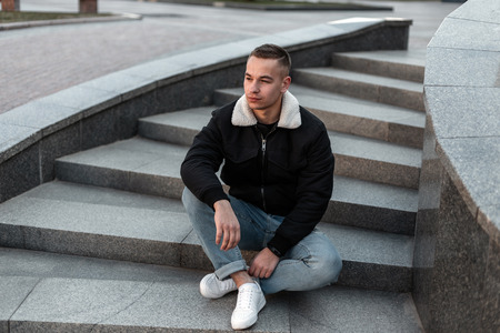 Young handsome man in blue jeans in a black jacket in white sneakers with a hairstyle sitting on a vintage stone staircase in the city. Nice guy resting  on a warm spring day. Trendy menswear.