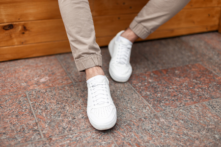 Fashionable mens white leather sneakers. Stylish mens shoes. Casual design. Close-up of male legs. Stock Photo