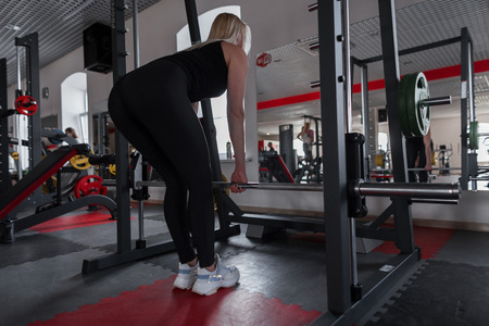 Athletic young beautiful woman in black sportswear doing exercises with a metallic vulture in a modern gym. Girl trainer in training. Stock Photo