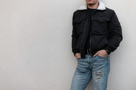 Young stylish man in a black trendy jacket with a white collar in vintage blue jeans in a black t-shirt stands near the gray wall. Fashionable men's outerwear. Street style. Close-up of a male body.